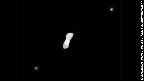Kleopatra (center) is shown with its moons AlexHelios and CleoSelene, which are the two small white dots (top right and bottom left).