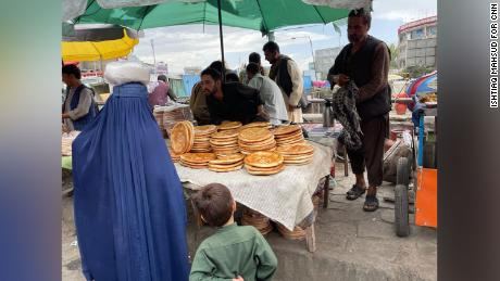 A woman in a blue burqa buys naan bread in the Kabul bazar.