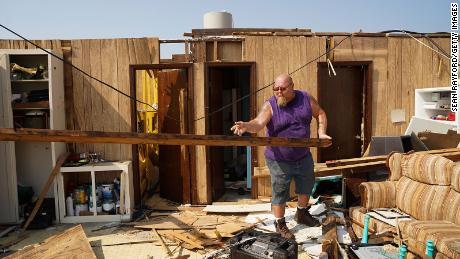 Greg Knight tosses a wooden beam at his storm-damaged house in Grand Isle, Louisiana.