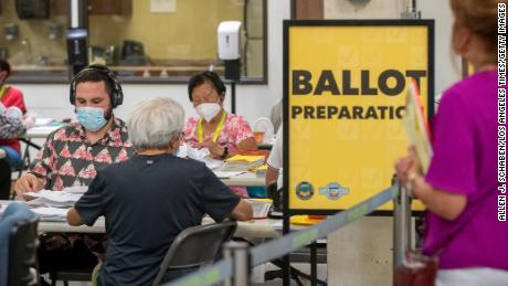 An observer watches election workers process ballots at the Orange County Registrar of Voters in Santa Ana, California, on Thursday, Sept. 9, 2021.