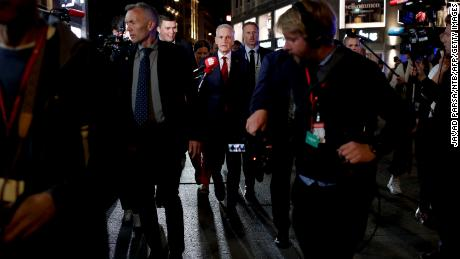 Labour leader Jonas Gahr Støre, center, surrounded by security guards and journalists in teh early hours of Tuesday.