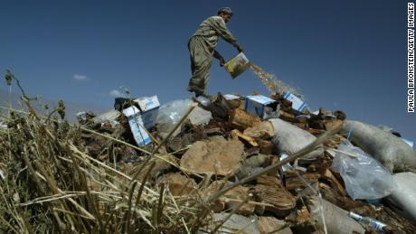 An Afghan worker pours gasoline on a large pile of illegal drugs that were destroyed in September 2004 in Kabul.