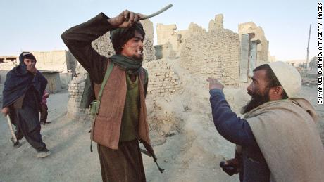 A Taliban militiaman arrests and beats a man who was allegedly found in possession of half a kilogram of opium in Kabul in November 1996.
