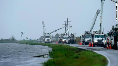 Utility crews on Tuesday replace power poles destroyed by Hurricane Ida in Pointe-aux-Chenes, Louisiana.