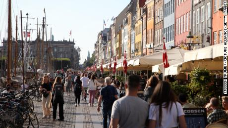 People walk along Nyhavn, a colorful harbor popular with visitors, in Denmark's capital, Copenhagen, on September 3.