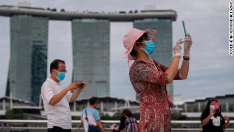 A woman wearing mask and gloves takes pictures at Singapore's Marina Bay on August 1, 2021.