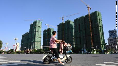 A woman riding a scooter past the construction site of an Evergrande housing complex in Zhumadian, Henan province on Sept. 14, 2021.