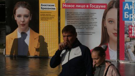 लोग 5 सितंबर को स्टेट ड्यूमा चुनाव के लिए एक निर्दलीय उम्मीदवार अनास्तासिया ब्रायुखानोवा के पोस्टरों पर चलते हैं।