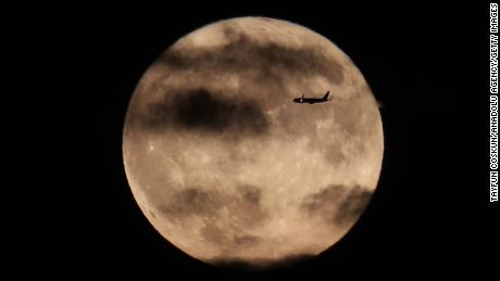 A plane flies past the harvest moon as it rises behind the Statue of Liberty in New York City, October 1, 2020.