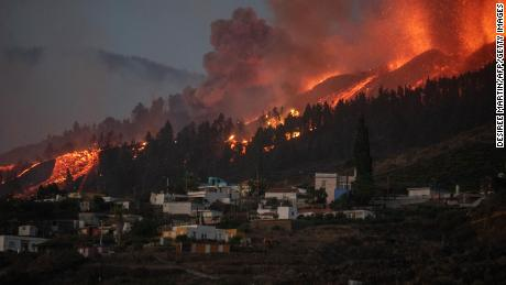 A river of lava flowing from the volcano approaches houses on Sunday.