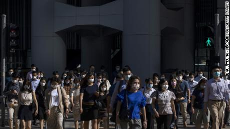 Morning commuters wearing protective masks cross a road in Central, Hong Kong on Aug. 18.
