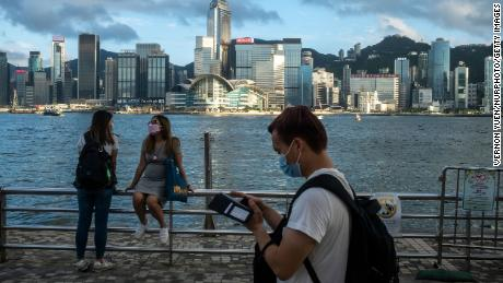 Pedestrians in front of the Hong Kong skyline in May.