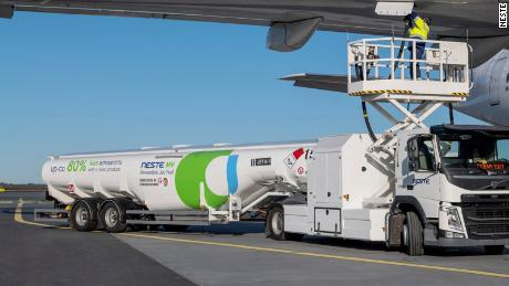 A tanker truck fuels a plane with SAF produced by Finland's Neste at Helsinki Airport.