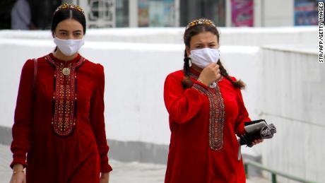 Turkmen women wearing face masks walk in Ashgabat on July 13, 2020.