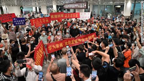"""Crowds hold banners and placards reading """"welcome home Meng Wanzhou"""" as they wait for Huawei executive Meng Wanzhou at Shenzhen Bao'an International Airport on September 25."""