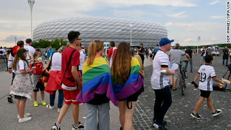 Fans wearing the rainbow flag outside of the Allianz Arena at Euro 2020