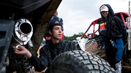 Racer Seth Quintero and Mia Chapman looking at one of the UTVs ahead of the race.