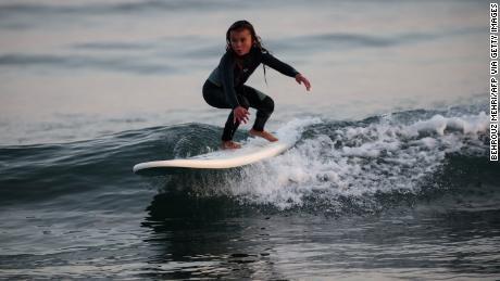 Brown surfs at a beach in Takanabe town, Miyazaki prefecture.