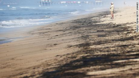 A person stands near oil washed up on Huntington State Beach in California on October 3.