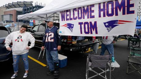 New England Patriots fans tailgating near a sign greeting the return of Brady.