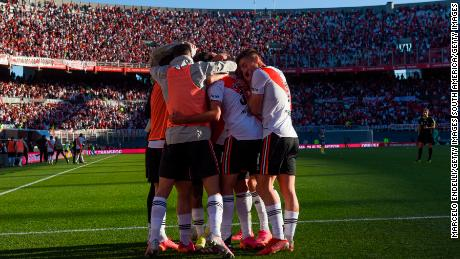 River Plate players celebrate in front of a packed stand.