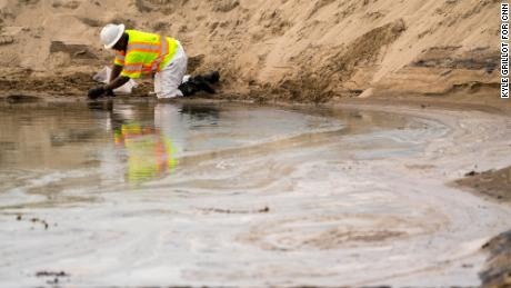 Crews work to clean the oil from the area in Huntington Beach.
