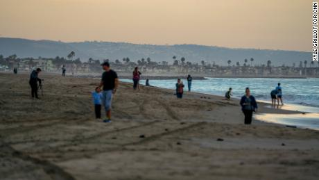 Beach goers wander the shore in the affected area off the coast of Huntington Beach.