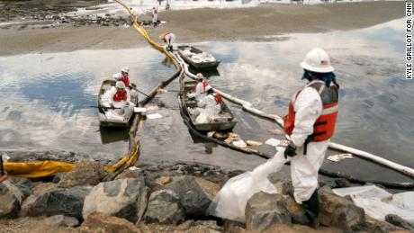 Patriot Environmental employees work to clear oil from the surface of the water inside Talbert Marsh.