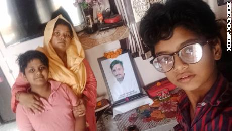 Pooja Sharma ir jos vaikai namuose prieš jos velionio vyro, mirusio nuo COVID-19 balandžio mėnesį Delyje, Indijoje, nuotrauką.