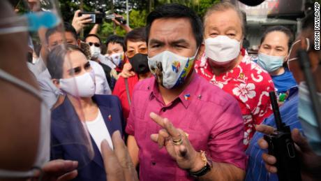 Išėjęs į pensiją filipiniečių bokso herojus ir senatorius Manny Pacquiao, centre, kalbasi su policija šalia žmonos Jinkee, kairėje, prieš paduodamas kandidatavimo pažymėjimą spalio 1 dieną Maniloje.