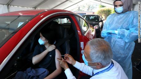 """Spalio 3 d. Sidnėjuje, Australijoje, gydytojas skiepija """"Pfizer"""" vakciną klientui """"Belmore Sports Ground"""" skiepijimo centre."""