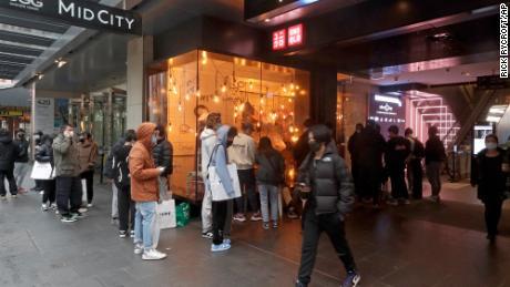 Spalio 11 d. Po daugiau nei 100 dienų uždarymo klientai stoja į parduotuvę Sidnėjuje.