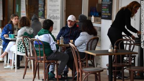 Vakarieniautojai sėdi kavinėje Sidnėjuje, Australijoje, spalio 11 d., Kai miestas išeina iš uždarymo.