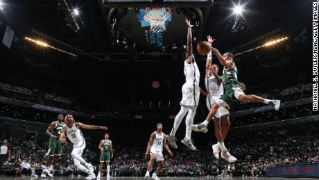 Justin Robinson of the Bucks drives to the basket during the preseason game against the Nets.