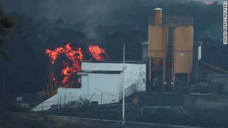 Lava rolls down behind a cement factory earlier this month as the Cumbre Vieja volcano continues to erupt on La Palma.