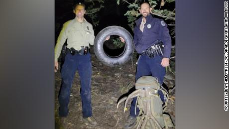 Wildlife officers Murdoch (left) and Swanson (right) hold up the tire that was on this bull elk for over two years.