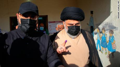 Populist Shia cleric Muqtada al-Sadr displays his ink-stained finger that shows he voted, at a polling center during the parliamentary elections in Najaf, Iraq, Sunday, Oct. 10, 2021.