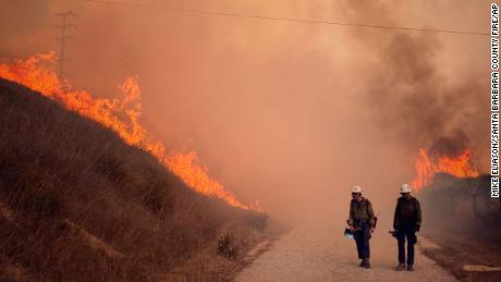 Santa Barbara County Fire Hand Crew members fight fire with fire and burn off pockets of grass along northbound Highway 101 north of Arroyo Hondo Canyon in Santa Barbara County, California, Tuesday.