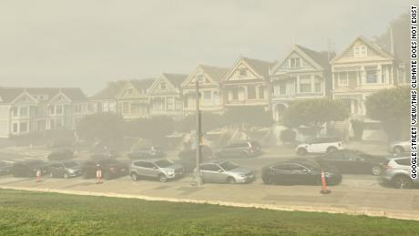 """ThisClimateDoesNotExist uses AI to show how places might look due to climate change; here, a Google Street View image of San Francisco's """"Painted Ladies"""" homes are depicted by the tech as shrouded in smog."""