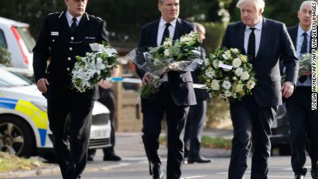 Britain's Prime Minister Boris Johnson (right), Britain's main opposition Labour Party leader Keir Starmer (center) and senior police officer Ben-Julian Harrington carry floral tributes to Belfairs Methodist Church in Leigh-on-Sea on Saturday.