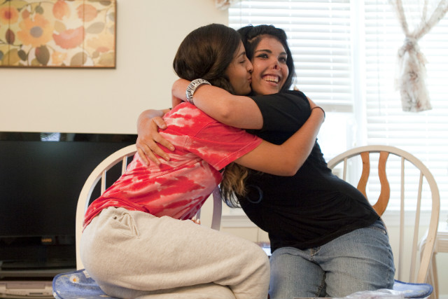 Aesha, right, hugs Miena, a high school honors student and athlete who has become a sister to her.