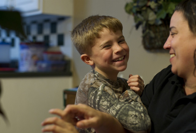 Joel Evans, 7, and his mom, Sabrina Evans, laugh at their home.