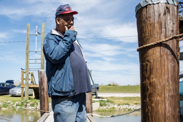 Byron Encalade stands on the dock in Pointe a la Hache, Louisiana.