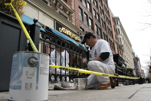 Workers at a Boylston Street restaurant paint over the damage caused by the Boston marathon bombings.