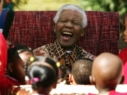 Former South African President Nelson Mandela jokes with youngsters as they celebrate his 89th birthday at the Nelson Mandela Children?s Fund in Johannesburg 24 July 2007