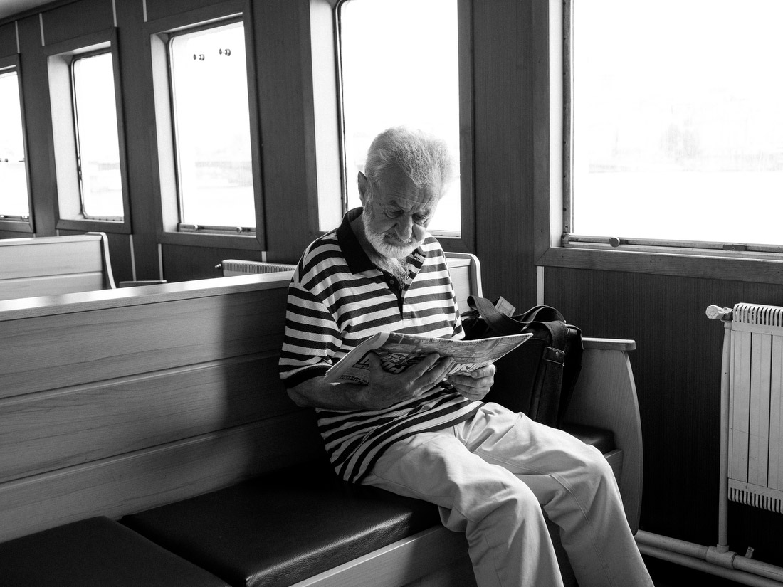 A man reads about the airport attack on a ferry.