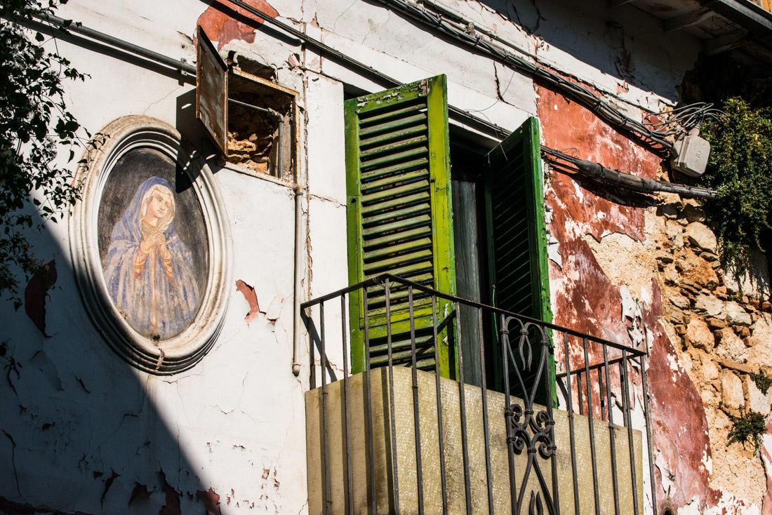 A religious fresco adorns a damaged house.
