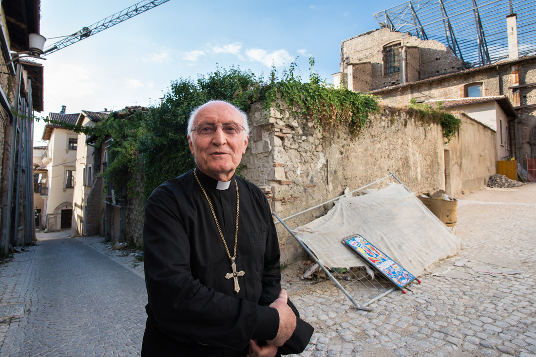 Monsignor Paolo De Nicolo tours the red zone. Visiting from Rome, he is set to perform Santa Messa, or 'Holy Mass,' at the Basilica Santa Maria di Collemaggio.