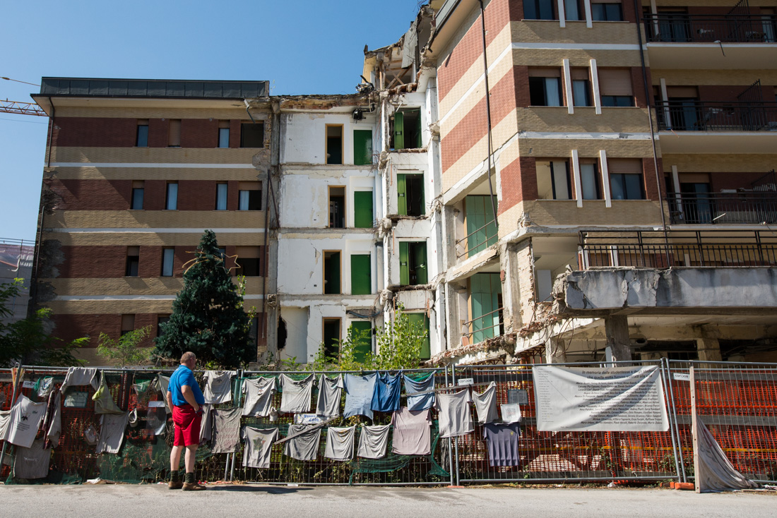 Giovanni Comoligio views a memorial for the 11 students who died in a university dormitory that collapsed during the earthquake.