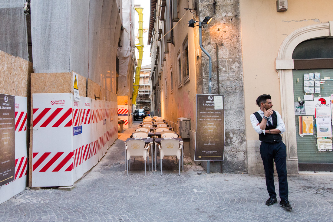 A server waits outside a restaurant before the Saturday dinner rush, on the main drag in the city center.